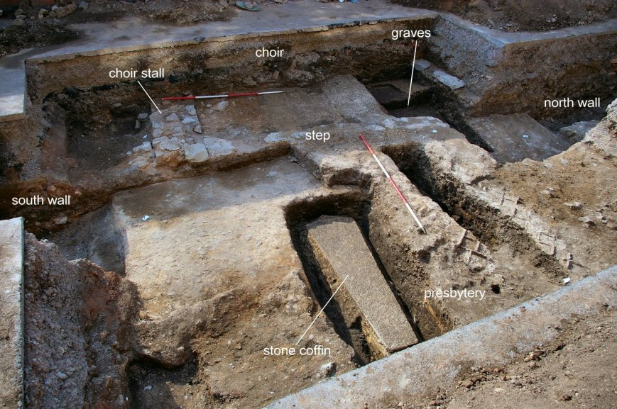 Trench 3 fully excavated, looking west. A medieval stone coffin and tile impressions in the presbytery can be seen in the foreground, with the remains of a choir stall behind.