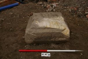 A carved stone plinth found during the excavation, perhaps a column base or statue base.