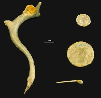 Roman metalwork from the site: (left) the handle from a copper-alloy jug. The handle is a 'dolphin' design and the remaining iron fragment at the top suggests a vessel with a hinged lid. (right, top-bottom) A 3rd/4th century coin, a 1st century coin and a copper-alloy pin.