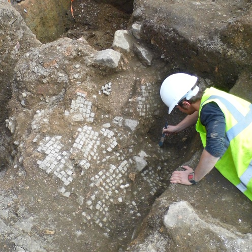 The remains of a Roman mosaic floor is carefully excavated. After the building containing the mosaic was demolished, the floor has broken and collapsed into a medieval ditch.