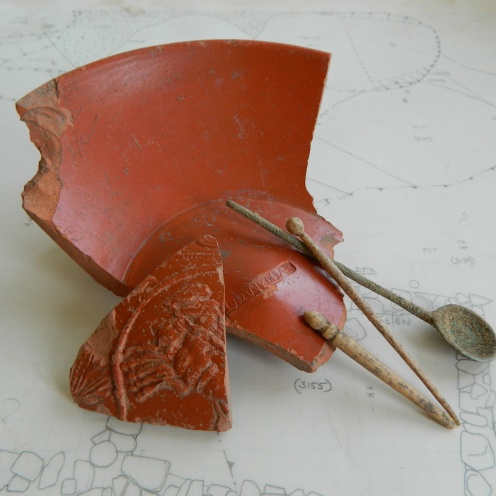 Some of the Roman artefacts discovered during the excavation – fine Samian table wares, bone hairpins and a copper spoon.