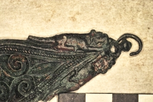 The strap end is decorated with crouching dogs on either side of its tapered end.