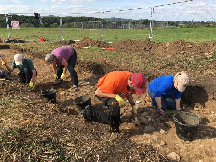 Uncovering the stone and earth bank of the outer earthwork in Trench 1
