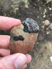 Iron slag sticking to a piece of medieval pottery.