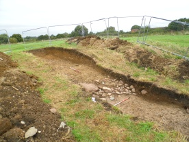 In Trench 2 the earth mound is found to have been deliberately constructed with a stone kerb running around its base.