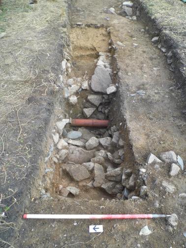 Excavation of the outer ditch in Trench 1 is hampered by a modern pipe and large quantities of tightly packed stone.
