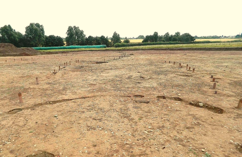 The post-alignment (right) and beam slot (left) marked out by land drains. Looking from one of the roundhouses.