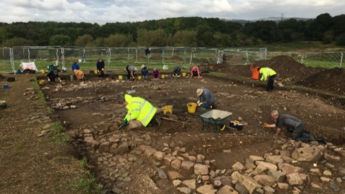 A photograph showing archaeologists excavating the manor house.