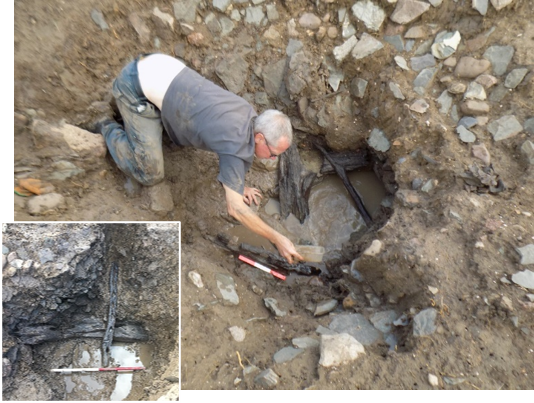 A photograph of an archaeologist excavating waterlogged medieval building timbers from a well.