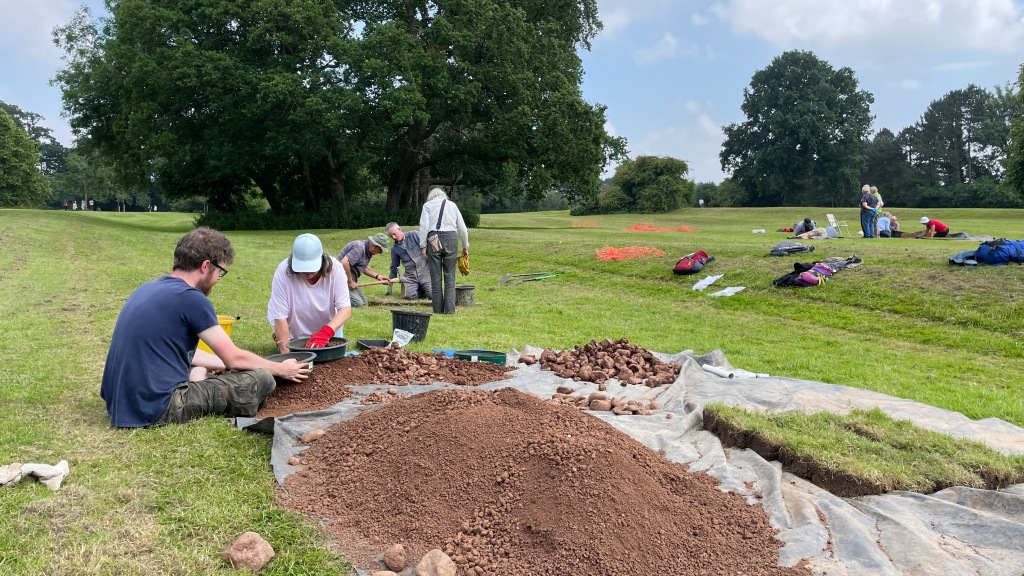 People digging test pits and sieving soil for finds in grass parkland.